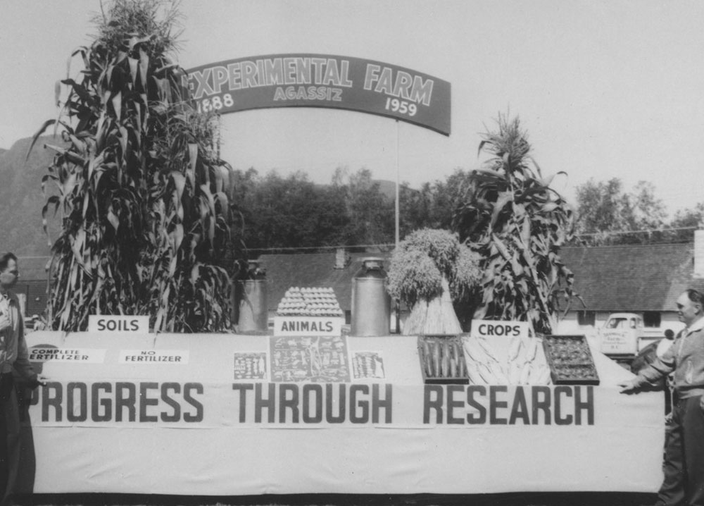 Black and white photograph of a farm display. There is an arch in the background with two high stalks of corn on each side naming the Experimental Farm Agassiz, 1888 to 1959. In the foreground, a table features a display of soils, animals, and crops with a sign hung on the front of the table promoting Progress through Research.