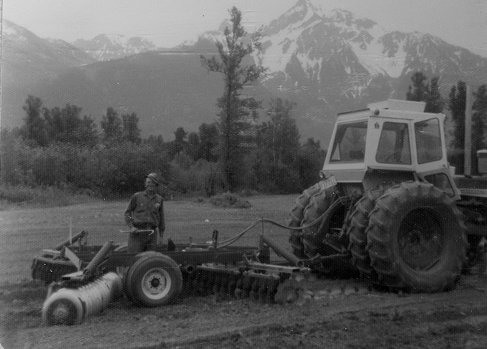Black and white photograph of a man with a tractor pulling discing equipment in a field and Mount Cheam in the background.