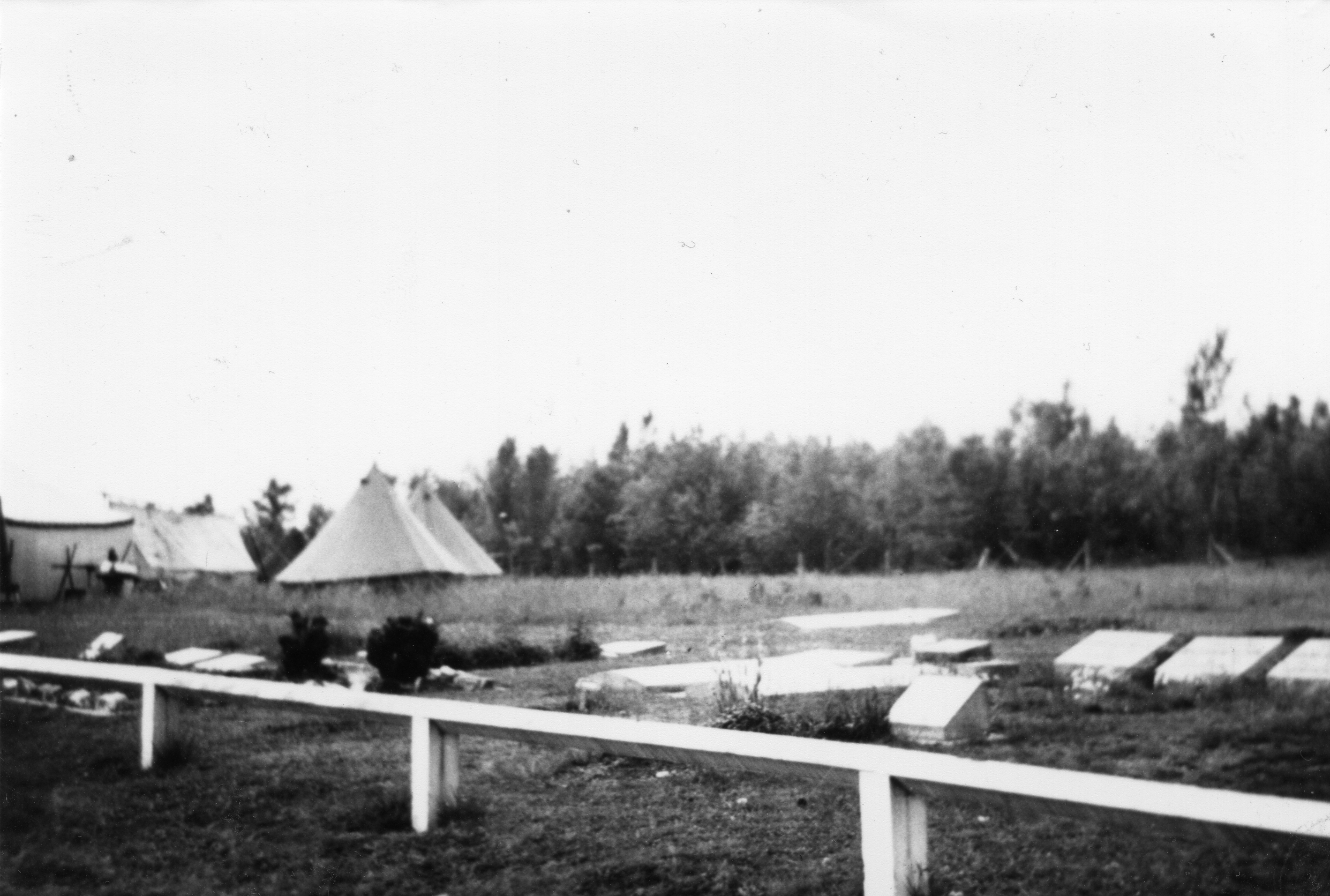 Black and white photograph of white tents next to a cemetery.