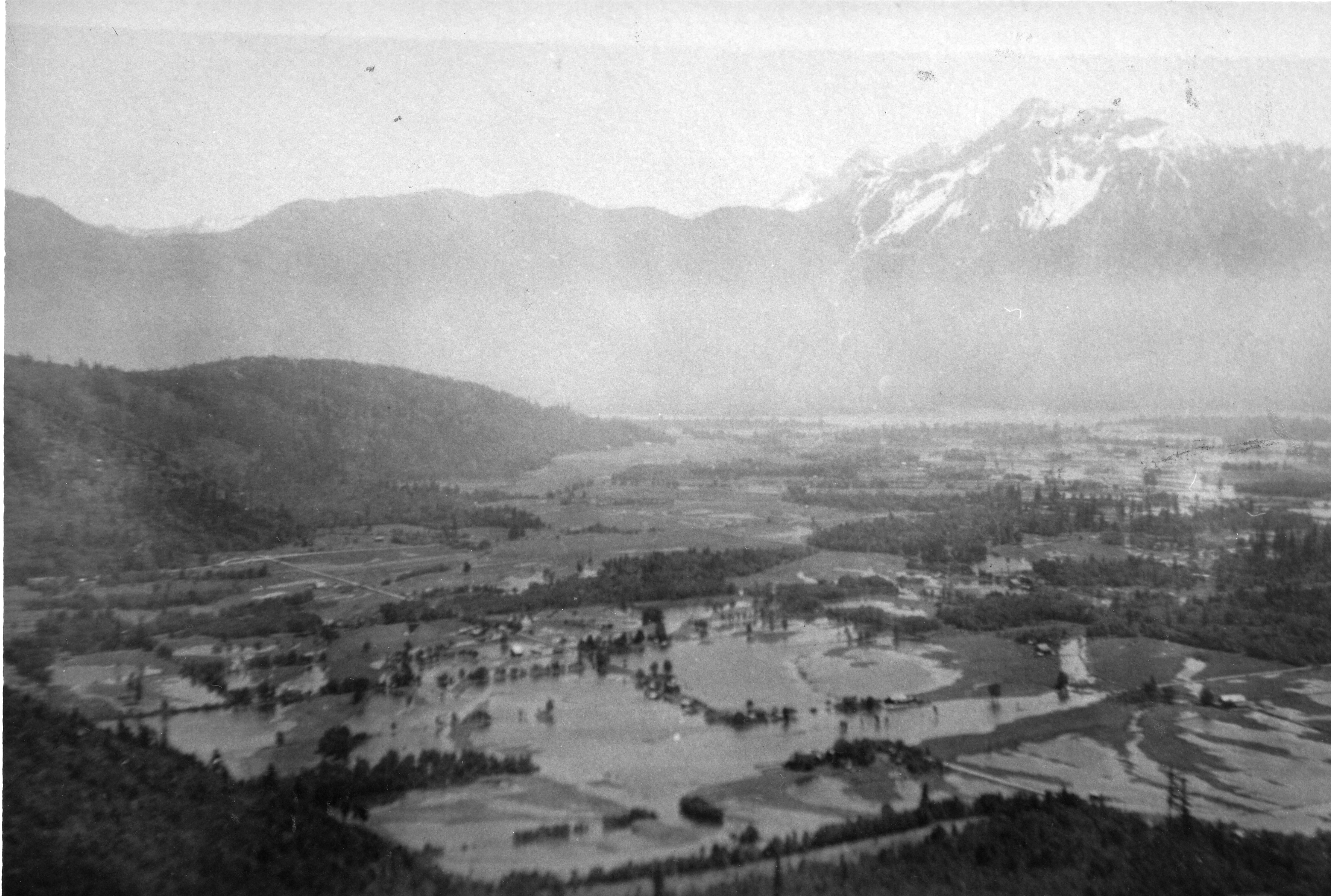 Black and white photograph of flooded fields with mountains in the background.