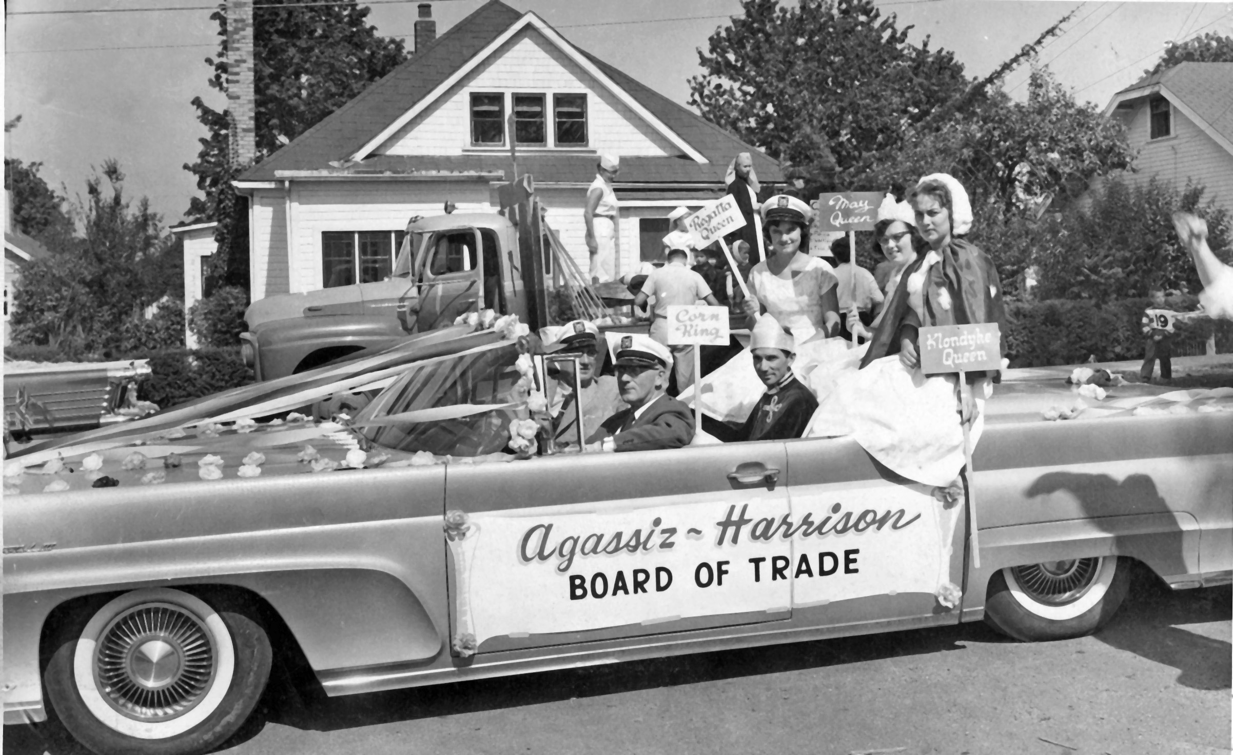 Black and white photograph of the Agassiz-Harrison Board of Trade car full of costumed adults in a parade, 1958.