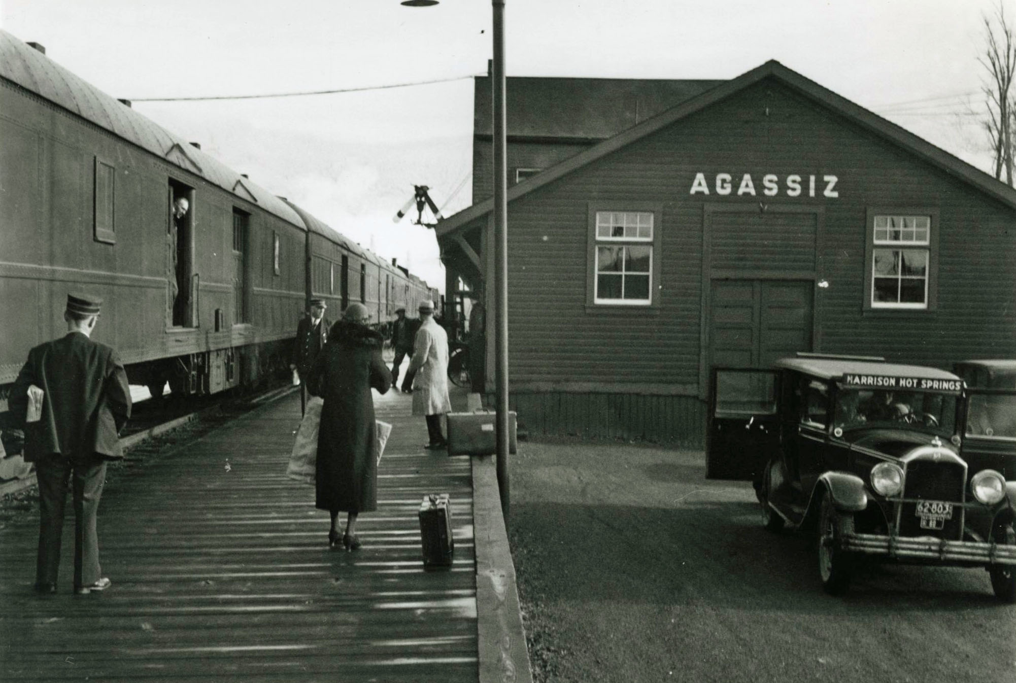 Black and white photograph of a train at the Agassiz station with passengers waiting on a platform. A Harrison Hot Springs taxi is in the foreground.
