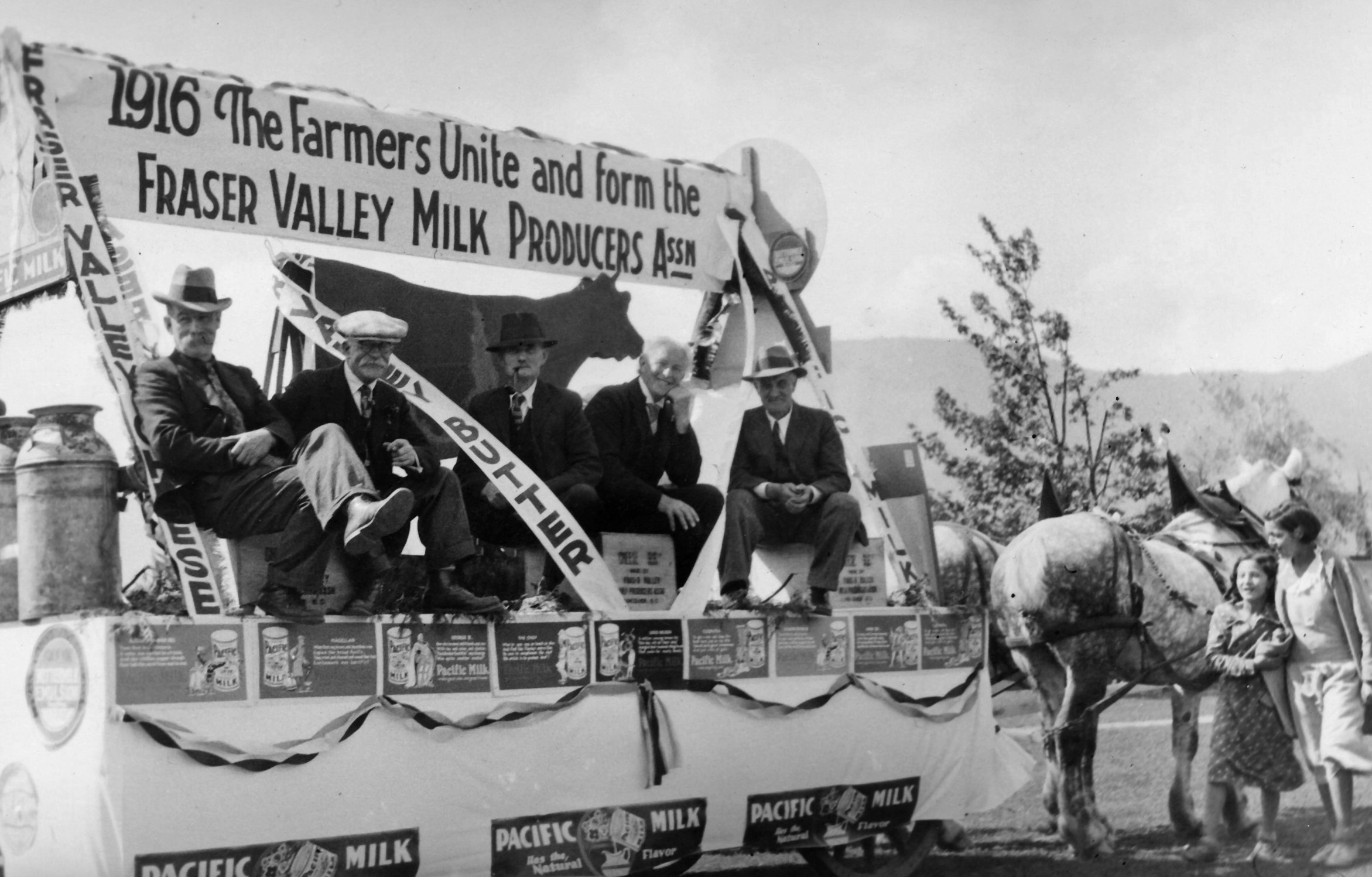 Black and white photograph of five men on a parade float pulled by a team of horses. There is a sign on the float, 1916 The Farmers Unite and form the Fraser Valley Milk Producers Assn. They are promoting Fraser Valley cheese, butter, and milk.