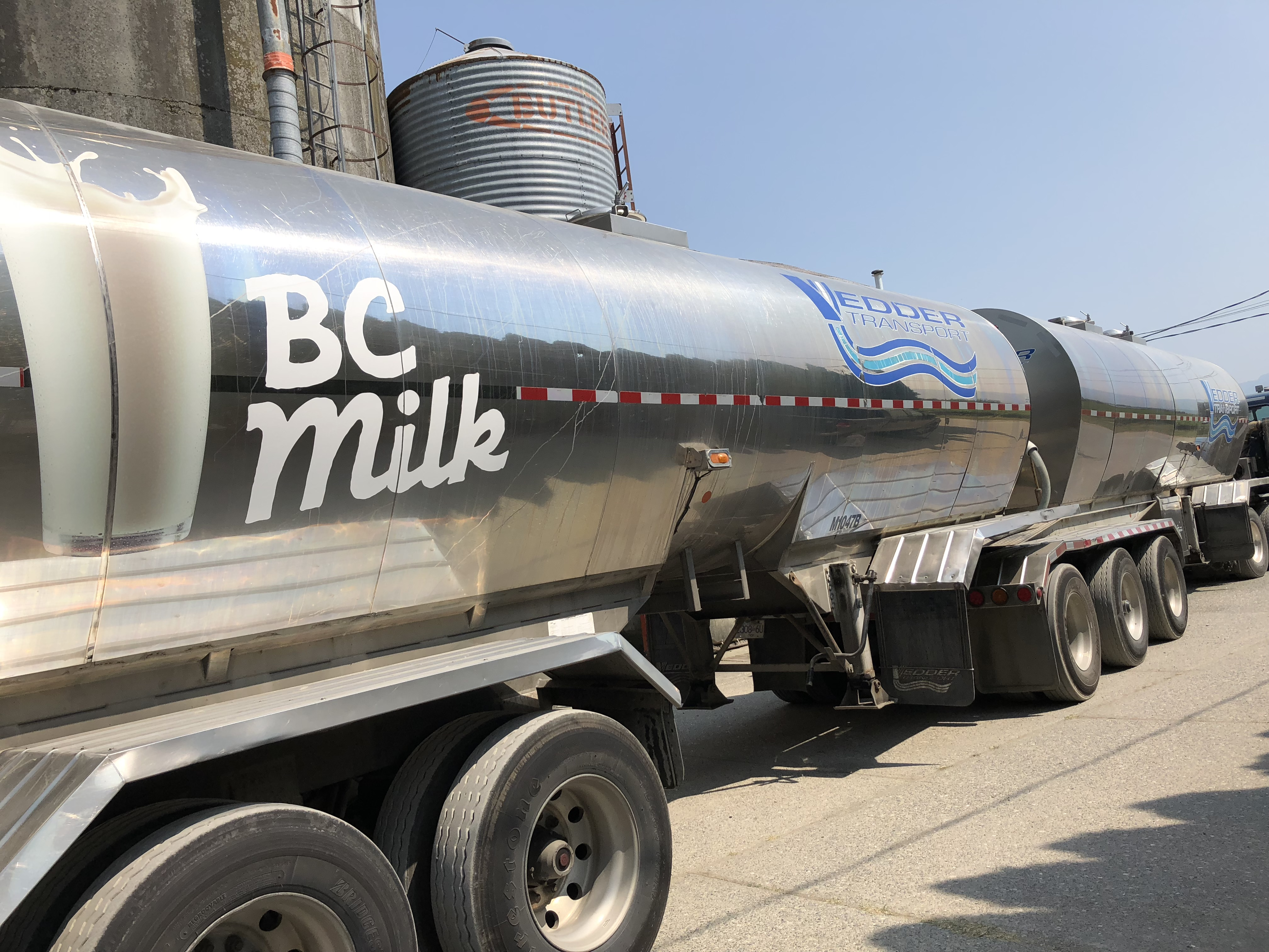 """Colour photograph of a BC Milk truck in front of silos. The sign on the truck reads """"Vedder Transport."""""""