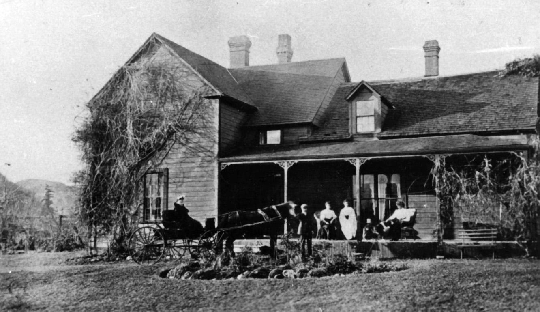 Photo en noir et blanc d'un Homestead. Des femmes sont assises sur la véranda et regardent deux personnes dans une calèche tirée par des chevaux.