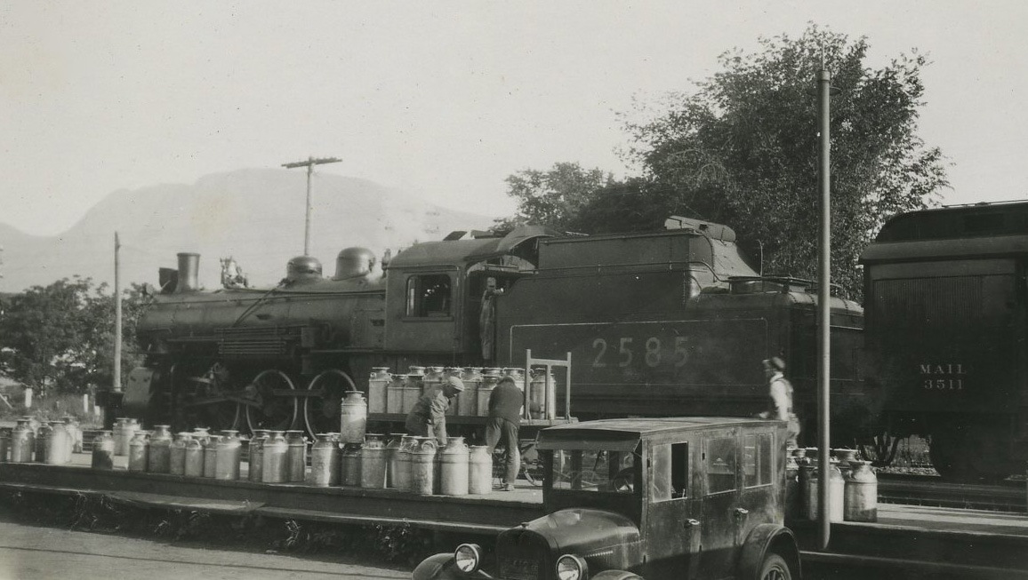Black and white photograph of men loading approximately 50 large milk cannisters onto a train. Cannisters are being loaded from a car in the foreground.
