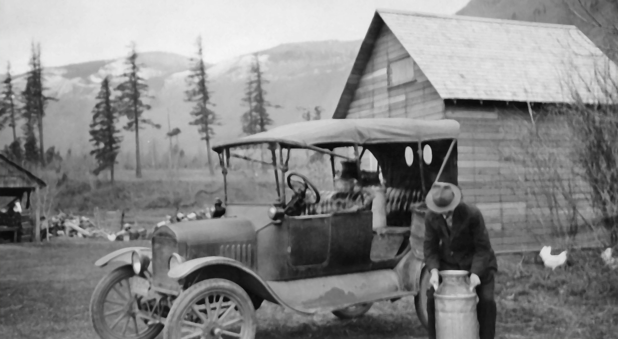 Black and white photograph of man loading milk cannisters into his Model T car.