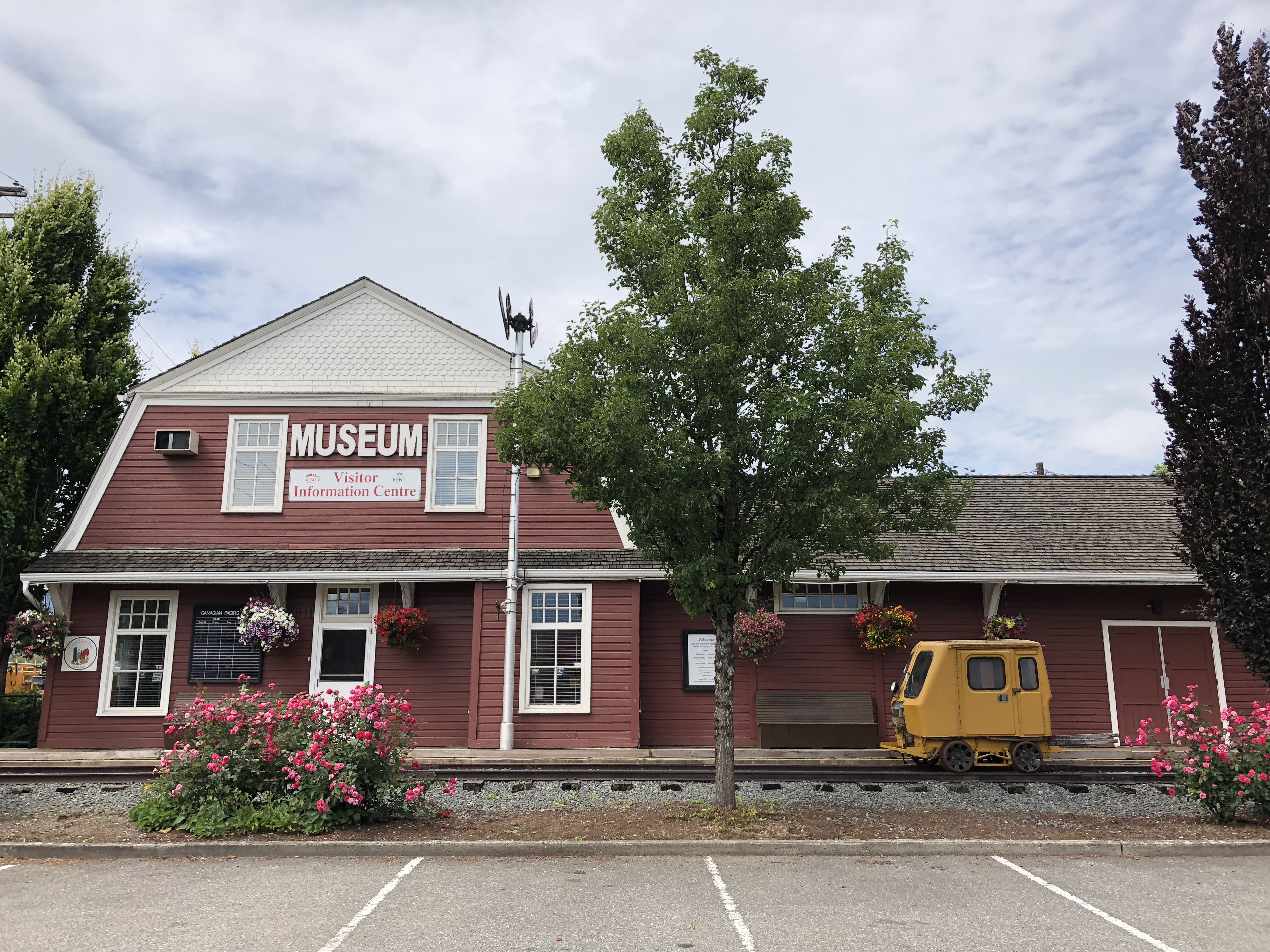 Colour photograph of a red and white barn-shaped historic train station, now the Agassiz-Harrison Museum and Visitor Information Centre.