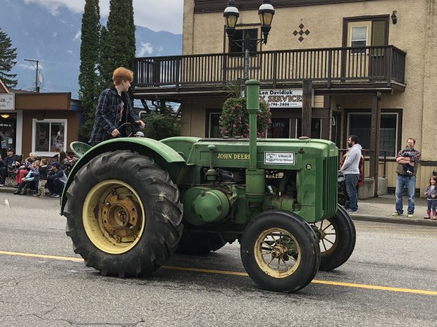 Colour photograph of a teenager wearing a plaid jacket driving an antique John Deere tractor in a parade.