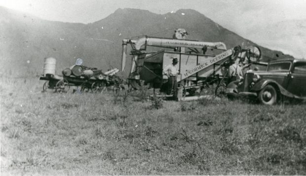 Black and white photograph of men working in a field using a McCormick-Deering thresher. A car is in the foreground and mountains are in the background. A wagon with barrels is adjacent to the thresher.