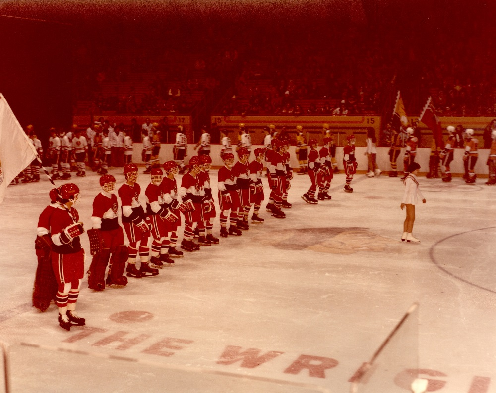 Colour photo showing a skating rink with dozens of hockey players in their uniforms. A young girl is skating in front of the boys. Spectators can be seen in the stands in the background.