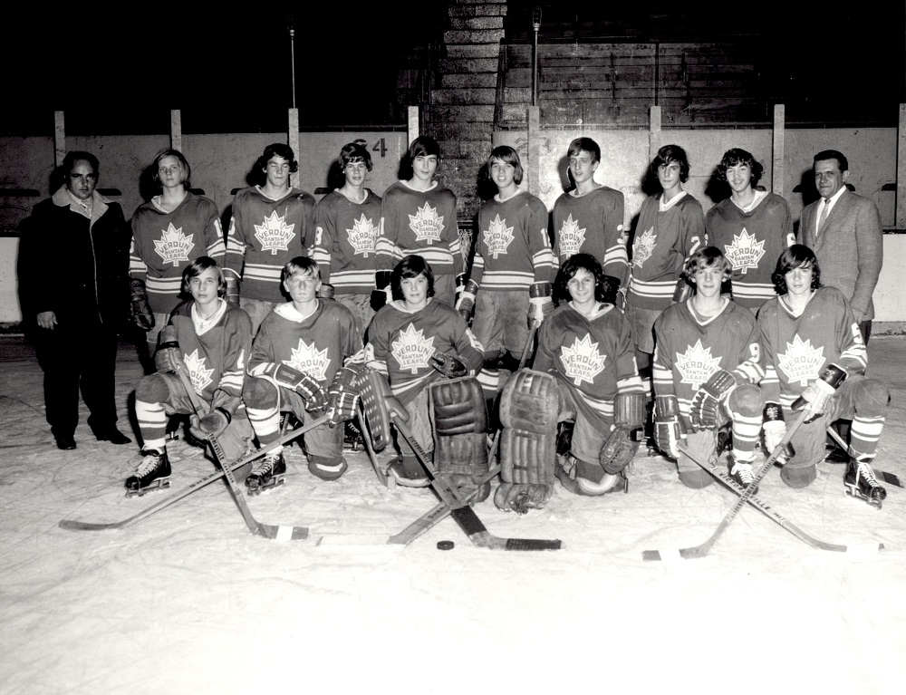 Black-and-white photo showing 14 boys in hockey uniforms, half of whom are kneeling on an ice rink with the other half standing behind them. A man is standing on each side of the boys.