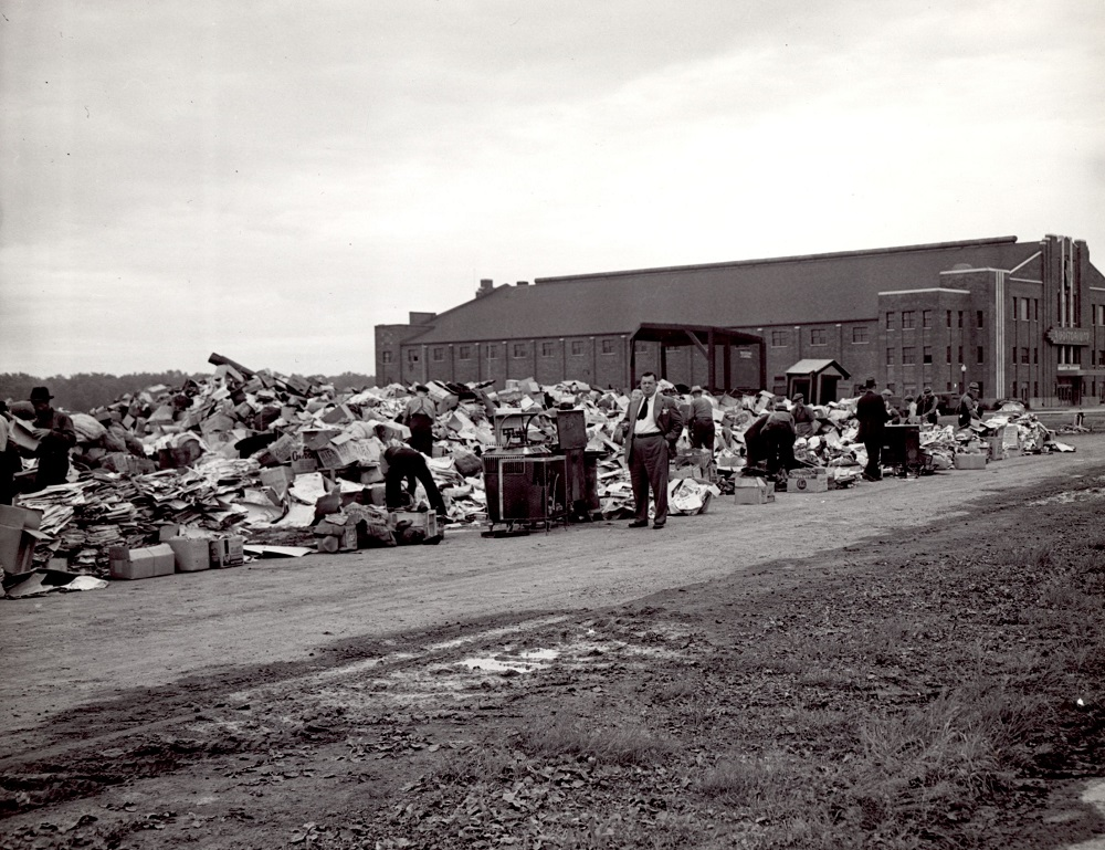 Black-and-white photo showing a collection spot located next to a building in the distance. About ten men are seen searching through this depot.
