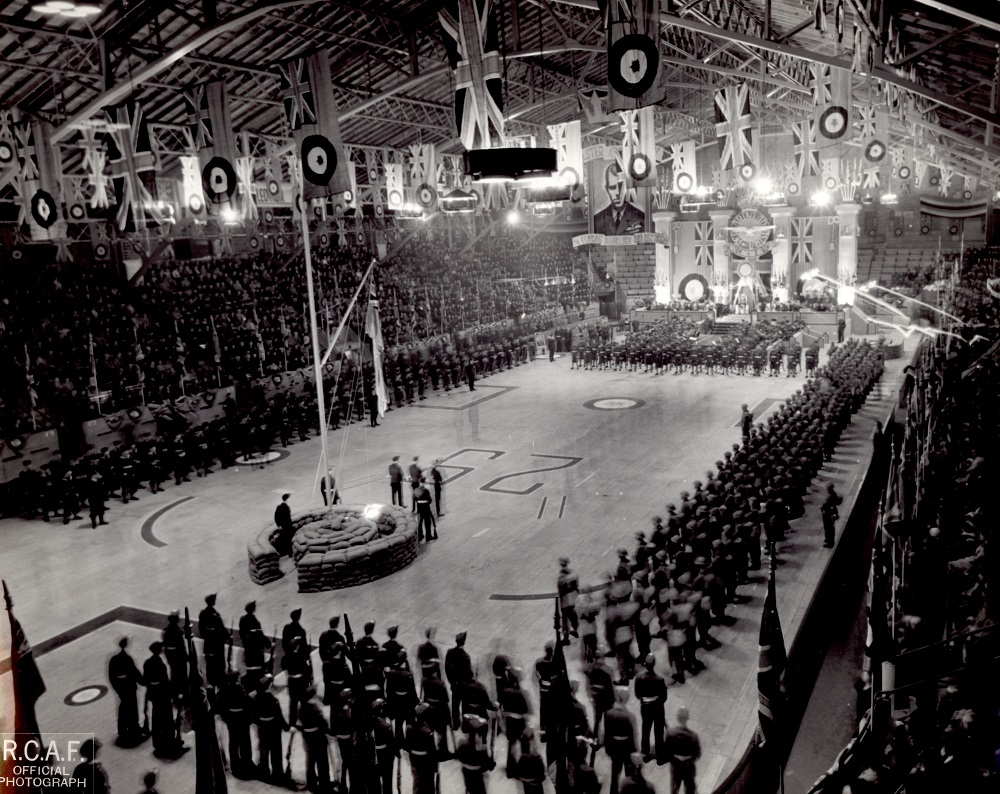 Black-and-white photo of a military gathering inside a building. A number of United Kingdom flags can be seen flying over the skating rink and a large crowd is in the stands.