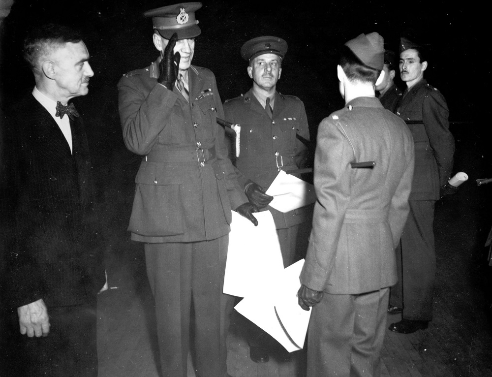 Black-and-white photo showing four servicemen in uniform and one civilian. Three soldiers are holding documents and one is giving a military salute.