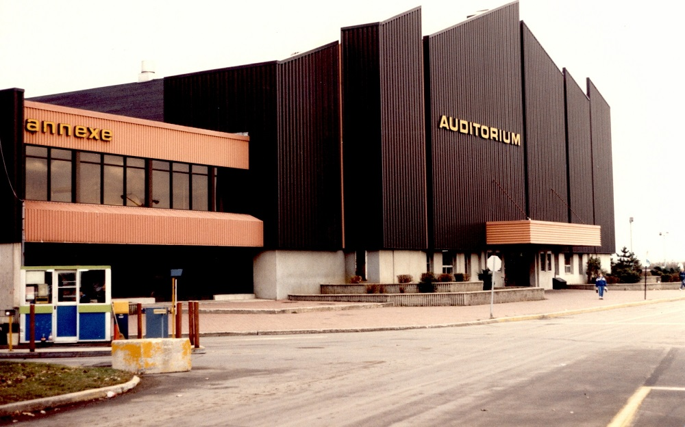 Colour photo showing two buildings: one with a black metal front and the other, orange.