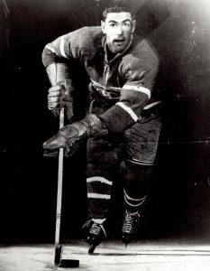 Photographie en noir et blanc d'un joueur de hockey portant le costume officiel des Canadiens de Montréal. On le voit de face avec son équipement en train de patiner.