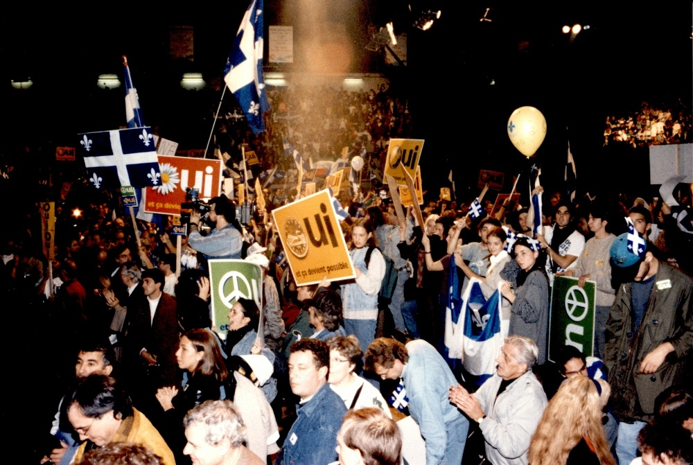 Colour photo showing a crowd of people in the stands holding Québec flags and placards.