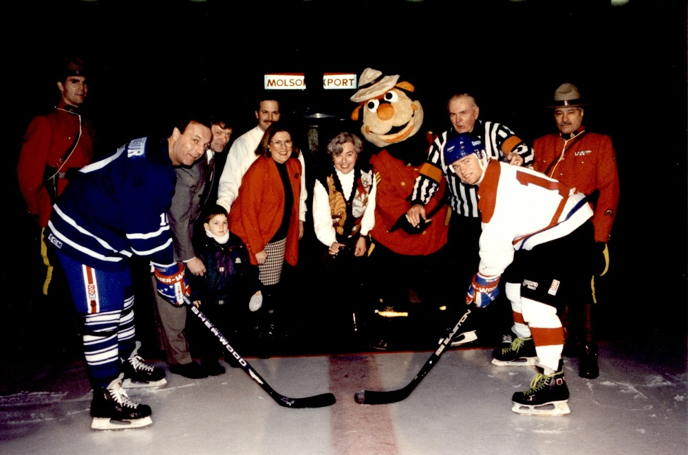 Colour photo showing two hockey players on an ice rink, waiting for the puck to drop. Behind them are five people on a carpet: a child, a man in a referee uniform, two RCMP officers and their mascot.