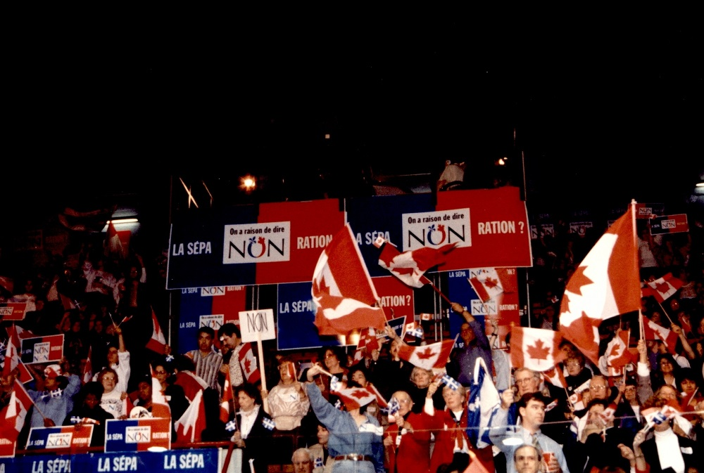 Colour photo showing a crowd of people in the stands, holding Canadian flags and placards.