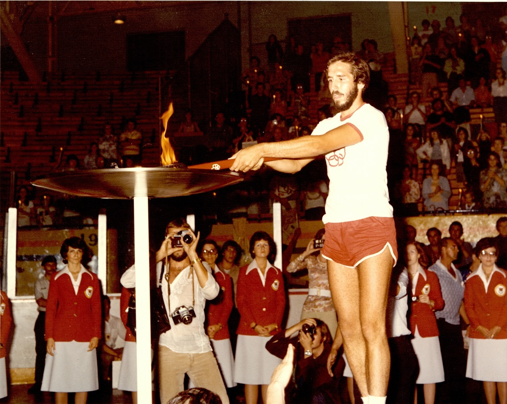 Colour photo of a man wearing orange shorts and a white sweater, holding a lit torch over a receptacle. A crowd can be seen in the background.