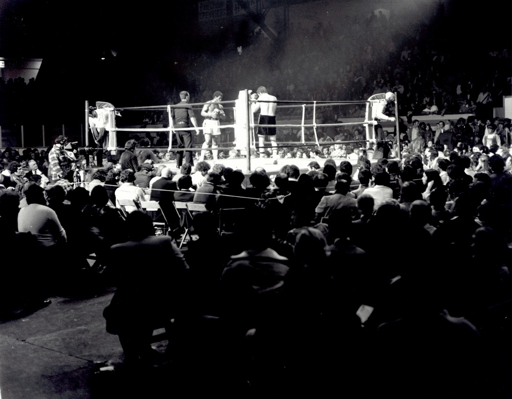 Black-and-white photo showing two men fighting in a boxing arena. A large crowd is cheering on the two athletes.