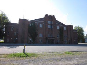 Photographie en couleurs sur laquelle on aperçoit un bâtiment en briques rouges dont l'entrée principale indique le nom du bâtiment : Aréna Jacques-Plante.