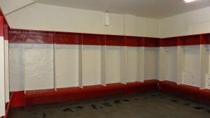 Photographie en couleurs montrant un long banc rouge surmonté de plusieurs cloisons verticales blanches. Chaque compartiment est également surmonté d'un petit casier rouge.
