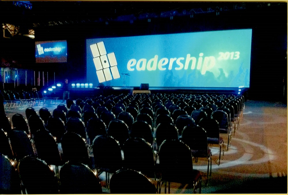 "Colour photo showing several rows of empty seats, turned toward a blue screen marked ""Leadership 2013""."