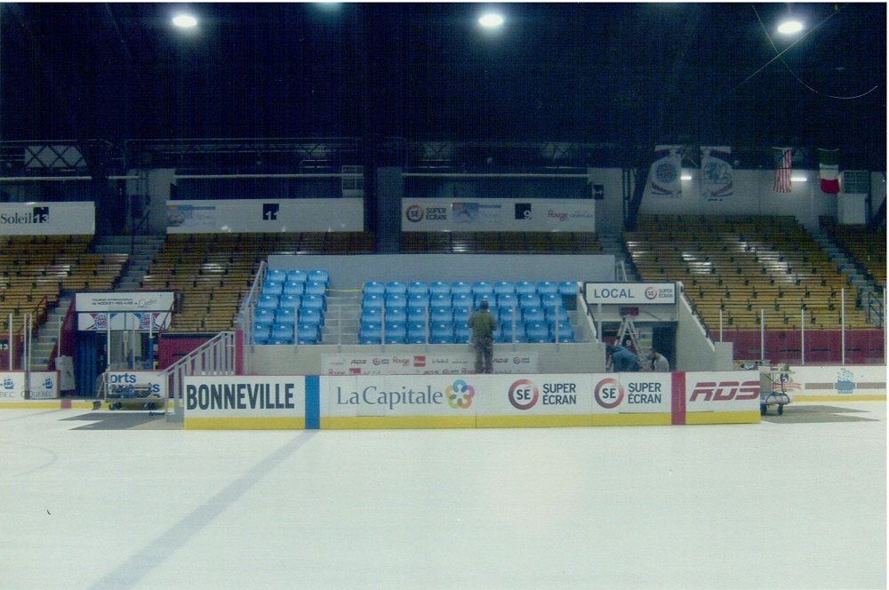 Colour photo showing, in front, a skating rink and its boards, on which several company names and logos are marked. In the middle are a number of rows of blue-coloured seating, surrounded by brown and yellow stands.
