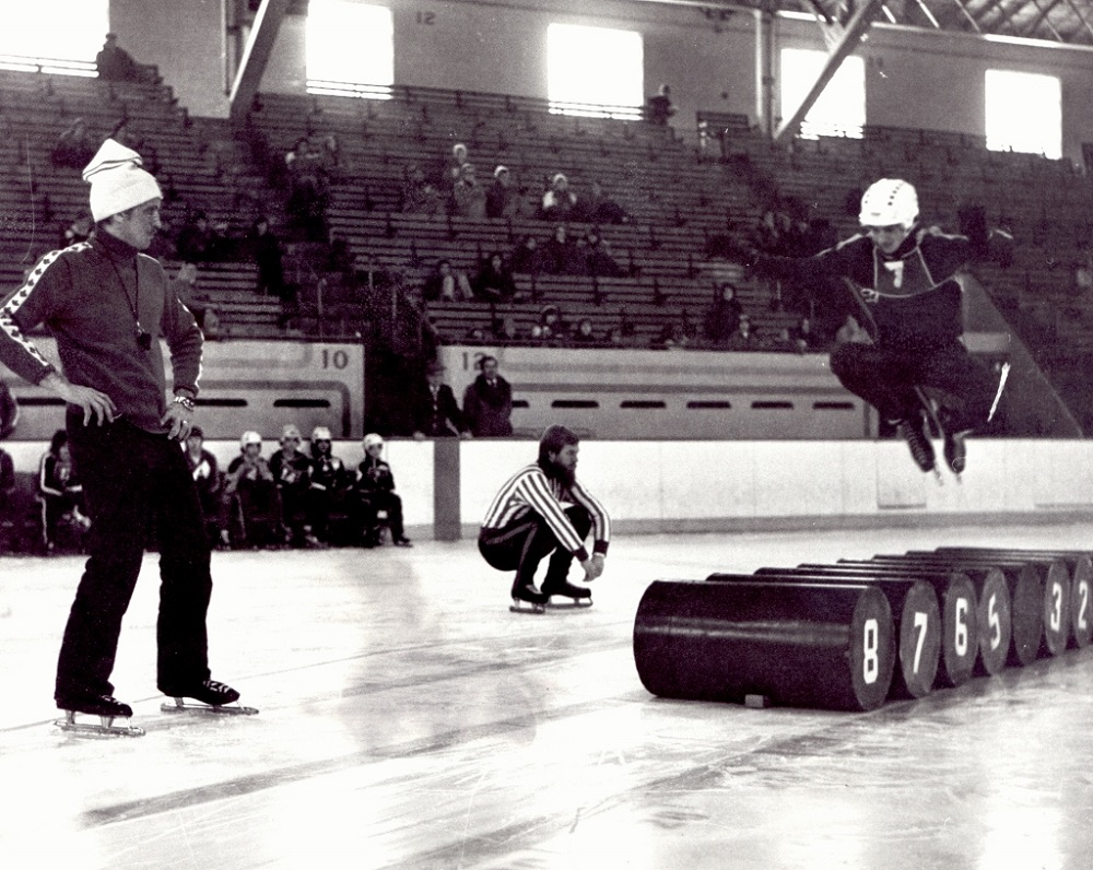 Black-and-white photo of three men on a skating rink. One of them is jumping over some barrels.