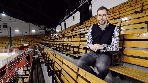 Colour photo of a man seating in a arena stand.