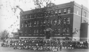 hundred schoolchildren pose in front of the Academy