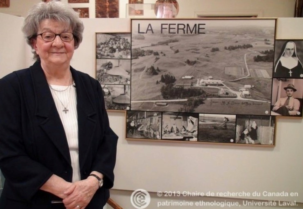 Woman standing in front of photographs of the farm.