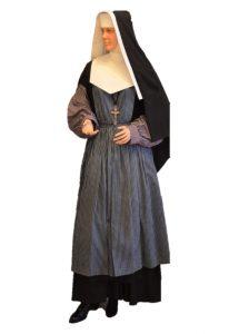 Un mannequin portant un habit de religieuse et un tablier.