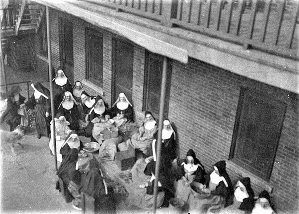 Black and white photo of a group of women wearing nuns' habits and aprons. They are peeling broad-beans, backs to the convent.