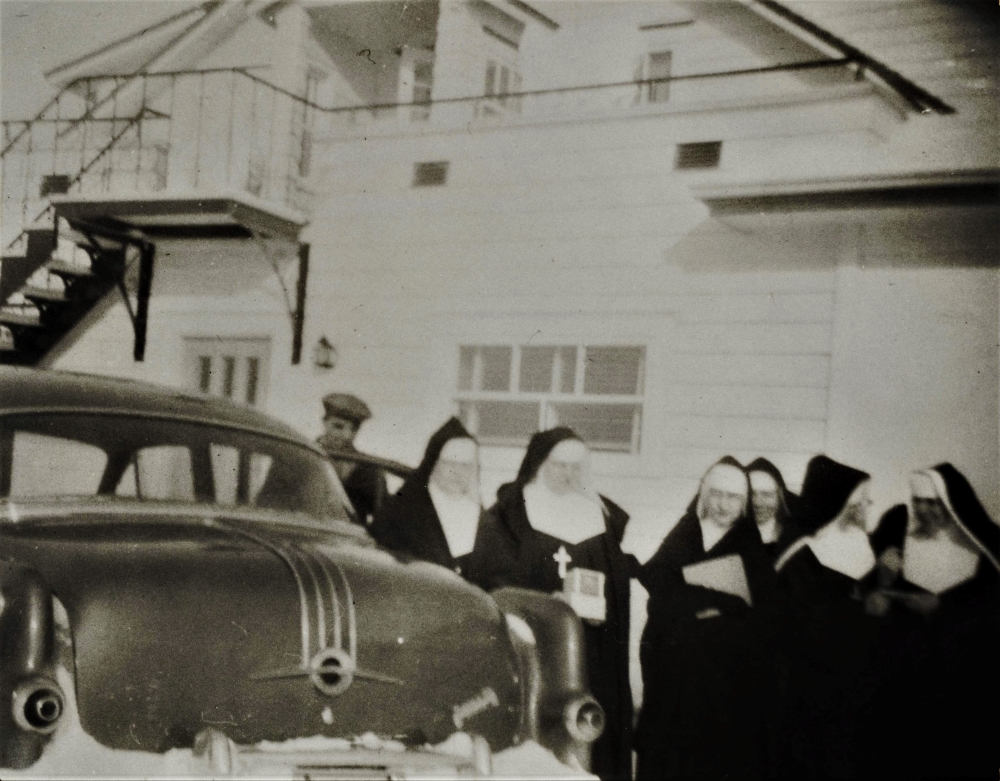 Group of nuns in front of a car.