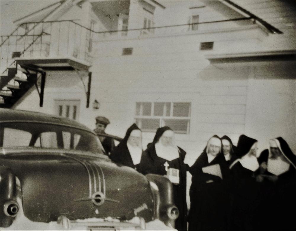 Un groupe de religieuses devant une voiture.