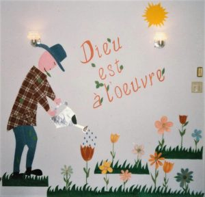 """Painting of someone watering plants, on a white wall, with the inscription """"God is at work""""."""
