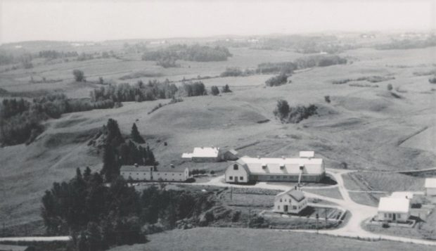 Black and white aerial view of farm buildings.