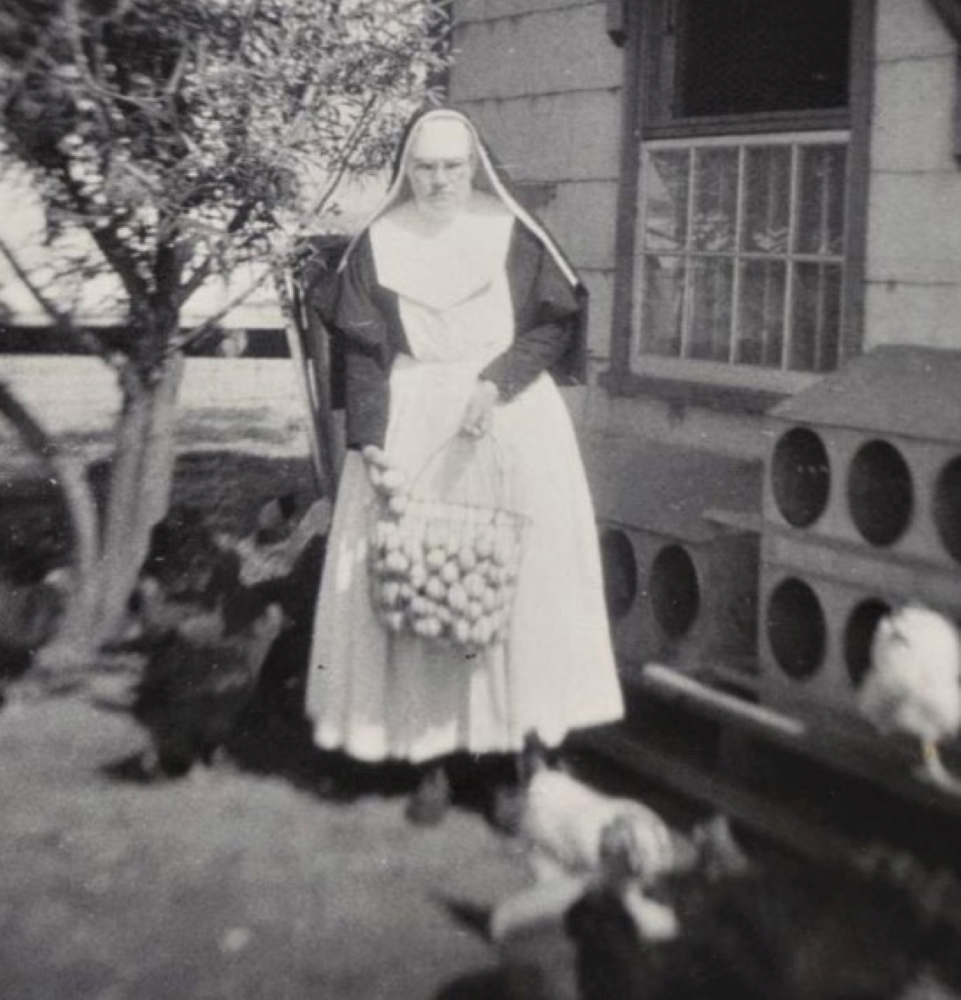 Black and white photo of a nun with a large metal basket filled with eggs.