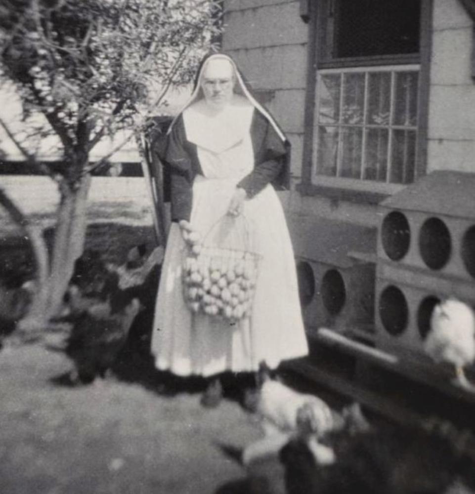 Photo en noir et blanc d'une sœur avec un gros panier en fer rempli d'œufs.