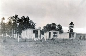 Black and white photo of three small fenced cabins.