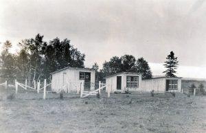 Photo en noir et blanc de trois petites cabanes clôturées.