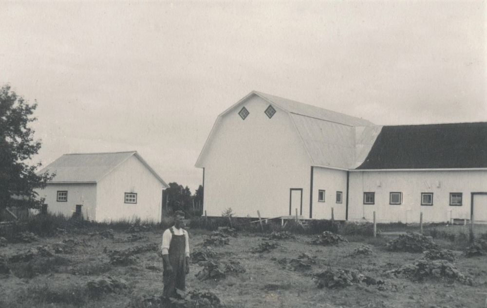 Black and white photo of a man in front of the farm abutting a field.