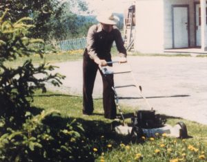 Colour photo of a man wearing a hat and mowing the lawn.