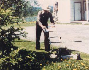 Photo en couleur d'un homme tondant le gazon avec un chapeau sur la tête.