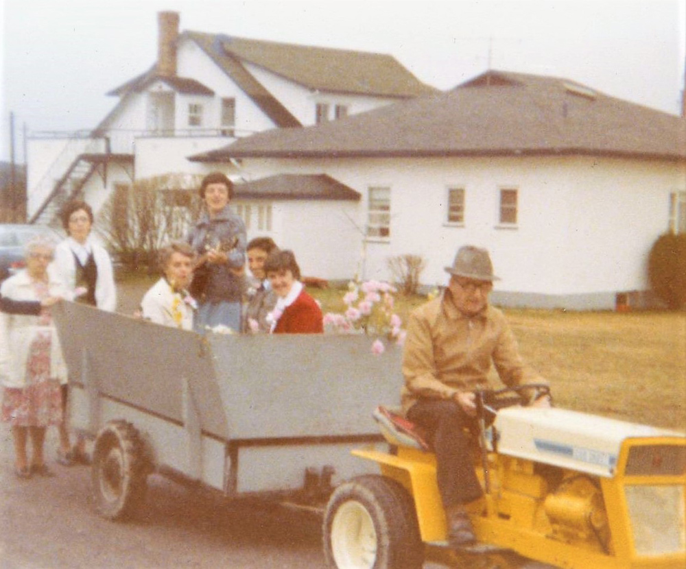 Colour photo of a man sitting on a small yellow tractor pulling a grey trailer where a few women are sitting. One of the women is holding a guitar. They are in front of the farmhouse.