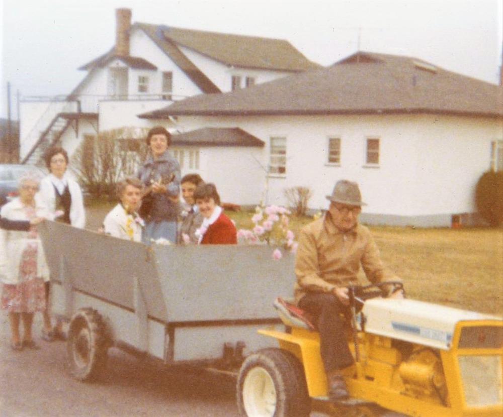 Photo en couleur d'un homme assis sur un petit tracteur jaune traînant une charrette grise où quelques femmes sont assises, dont l'une tient une guitare. Ils se trouvent devant la maison de la ferme.