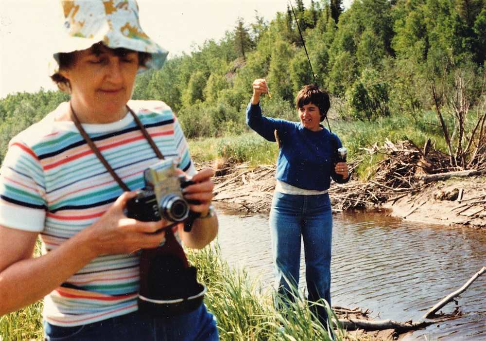 Colour photo of two women near a river. One is fishing while the other is holding a camera.